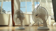 Two cooling fans inside on a hot summer day Stock Footage