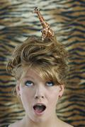 Shocked young woman with plastic giraffe in hair's Stock Photos