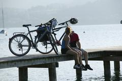 Germany, Bavaria, Couple with mountain bikes taking a break on landing stage - stock photo
