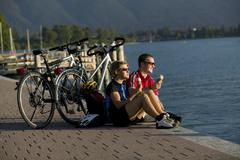 Germany, Bavaria, Tegernsee, Couple with mountain bikes eating ice cream - stock photo