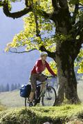 Austria, Tyrol, Ahornboden, Woman mountain biking - stock photo