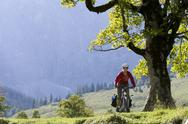 Stock Photo of Austria, Tyrol, Ahornboden, Woman mountain biking