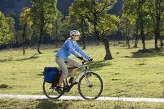 Austria, Tyrol, Ahornboden, Woman mountain biking, trees in background - stock photo