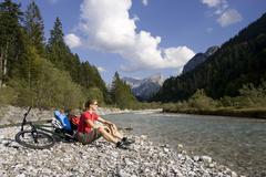 Stock Photo of Austria, Tyrol, Ahornboden, Mountainbiker riding across highway