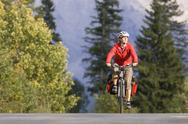 Stock Photo of Austria, Tyrol, Ahornboden, Mountainbiker riding across highway