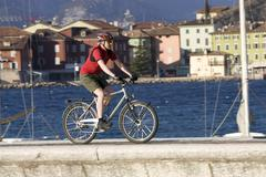 Italy, Trento, Torbino, Man mountain biking across pier Stock Photos