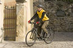Italy, Trento, Torbole, Mountaibiker riding across lane Stock Photos