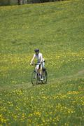 Germany, Bavaria, Oberland, Woman mountain biking across flowering meadow - stock photo