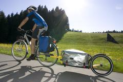 Germany, Bavaria, Man riding mountainbike with trailer - stock photo