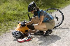 Germany, Bavaria, Oberland, Woman giving aid to fallen biker - stock photo