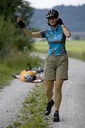Germany, Bavaria, Oberland, Woman gesturing, fallen biker in background - stock photo