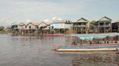 Cambodia river view of boats and houses on stilts Stock Footage