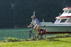 Austria, Tyrol, Achensee, Woman mountain biking lakeside Stock Photos