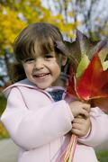 girl (4-5) holding autumn leaves, close-up - stock photo