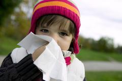Girl (4-5) blowing nose, close-up Stock Photos
