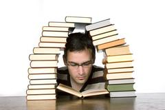 Young man reading by piled books, close-up Stock Photos