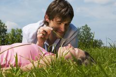 young couple in meadow, man holding blade of grass, close-up - stock photo