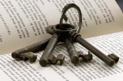 Keys on keyring lying on open book - stock photo