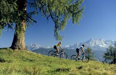 Austria, Salzburger Land, couple mountain biking, side view Stock Photos