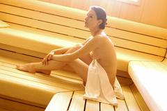 Naked woman sitting in sauna, side view Stock Photos