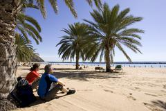 Spain, The Canary islands, Teneriffa, Couple relaxing on palm beach Stock Photos