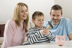 Parents and son (4-5) looking at piggybank, boy holding hammer Stock Photos