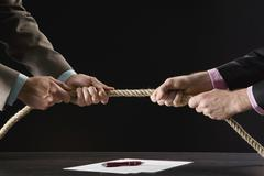 Stock Photo of businessmen pulling rope, close-up
