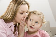 Mother and daughter (3-4) whispering, close up Stock Photos