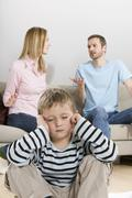 Parents arguing, boy (4-5) sitting in foreground - stock photo