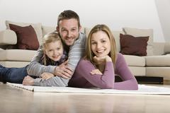 Stock Photo of Parents with daughter (3-4), relaxing at home