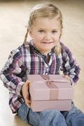 Little girl (3-4) holding gift parcel, smiling Stock Photos