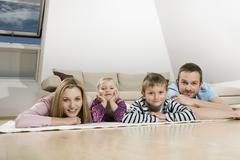 Family relaxing at home, smiling Stock Photos