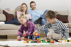 Family at home, children playing with building bricks Stock Photos