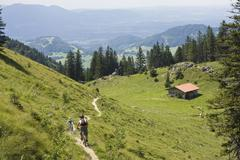 Germany, Bavaria, Chiemgau, Two men mountain biking across mountain scenery - stock photo