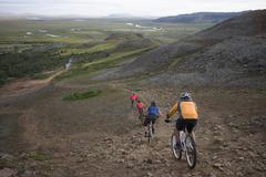 Iceland, Men mountain biking downhill, rear view Stock Photos