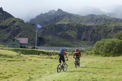 Iceland, Two Men mountain biking, Islandic ensign in background - stock photo