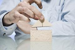 Stock Photo of Person building house with building bricks, close up