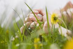 Stock Photo of Germany, Bavaria, Munich, Couple lying in meadow, holding hands, close-up