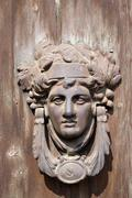 France, Alsace, Old copper door knocker with human face on wooden door Stock Photos