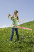 Germany, Bavaria, Munich, Girl (6-7) playing with hula-hoop - stock photo