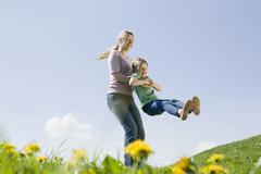 Germany, Bavaria, Munich, Mother swinging daughter (6-7) on meadow, fooling - stock photo