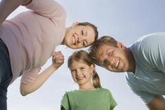 Germany, Bavaria, Munich, Family smiling, portrait, low angle view - stock photo