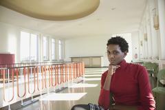 Germany, Leipzig, University student sitting in hallway, smiling, portrait Stock Photos