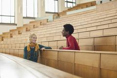 Germany, Leipzig, Students sitting face to face and talking in auditorium - stock photo