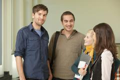 Germany, Leipzig, University students talking in university, smiling Stock Photos