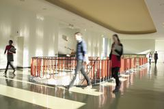 Germany, Leipzig, University students walking through corridor (blurred motion) - stock photo
