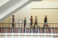 Germany, Leipzig, Group of university students walking through corridor (blurred Stock Photos