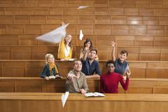 Germany, Leipzig, Group of university students throwing papers aeroplane and Stock Photos