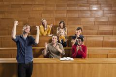Germany, Leipzig, Group of university students clapping hands and having fun in - stock photo