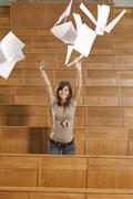 Germany, Leipzig, Young woman throwing papers and enjoying in auditorium - stock photo